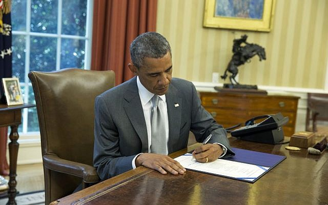 "President Barack Obama signs ""H.J. Res. 76,"" a bill that provides an additional $225 million in US taxpayer dollars for Israel's Iron Dome missile defense system, in the Oval Office of the White House, Monday, Aug. 4, 2014, in Washington. (photo credit: AP Photo/ Evan Vucci)"