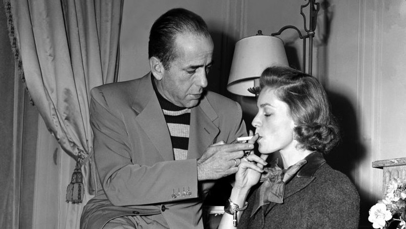 Actor Humphrey Bogart lights a cigarette for his wife, actress Lauren Bacall, in their room at the Ritz Hotel in Paris, France, during their vacation on March 26, 1951. (photo credit: AP Photo)