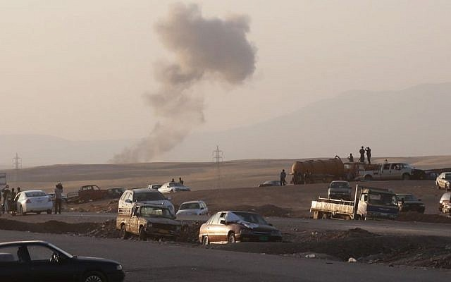 Smoke rises after airstrikes targeting Islamic State militants near the Khazer checkpoint outside of the city of Irbil in northern Iraq, Friday, Aug. 8, 2014.  (Photo credit: AP/ Khalid Mohammed)