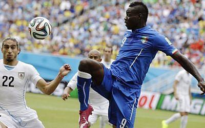Italy's Mario Balotelli  kicks the ball over Uruguay's Martin Caceres at the 2014 World Cup, June 24, 2014 (AP/Ricardo Mazalan)
