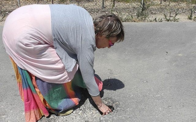 Adele Raemer, a resident of Kibbutz Nirim, which is located two kilometers from Gaza, shows a hole created by a rocket that fell dozens of meters from her home. (photo credit: Melanie Lidman/Times of Israel)