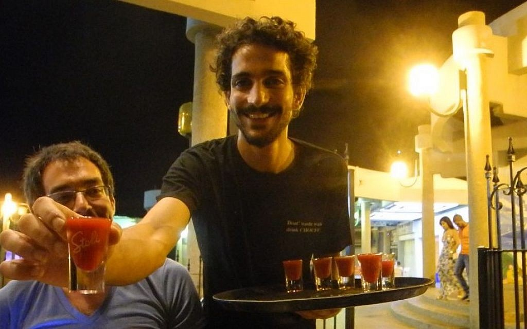 Ido Ozeri, one of the owners of Archies bar and restaurant in Ashkelon, passes out shots courtesy of a bar tab from American-Israeli Yigal Rechtman on Tuesday, the first night of the ceasefire. (photo credit: Melanie Lidman/Times of Israel)