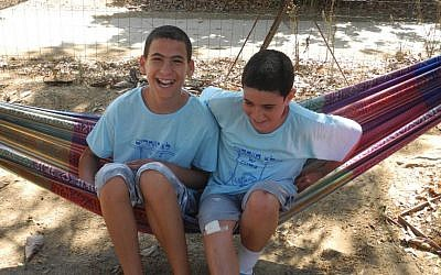 Brothers Regev (left) and Barak (right) Haglili, from Kibbutz Nirim in southern Israel, are thrilled to be back home despite frequent rockets, after spending the war in northern Israel with other children from the kibbutz.  (photo credit: Melanie Lidman/Times of Israel)