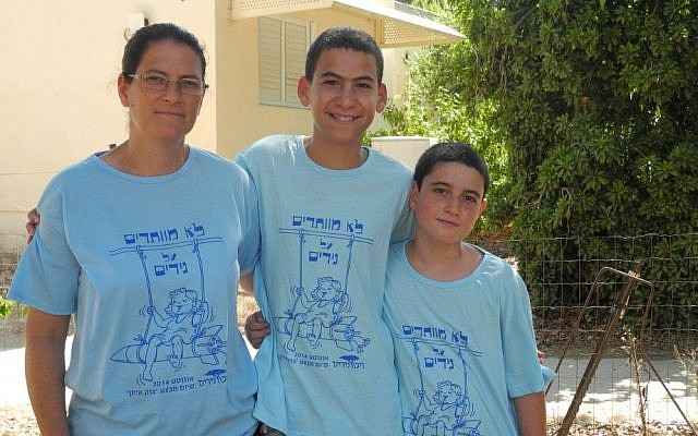 Ifat Haglili and her two sons outside their home in Nirim on their second day back. (photo credit: Melanie Lidman/Times of Israel)