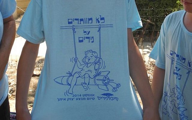 """Regev Haglili shows off a shirt made in honor of the residents return over the weekend, which says """"Were not giving up on NIrim"""" in Hebrew. (photo credit: Melanie Lidman/Times of Israel)"""