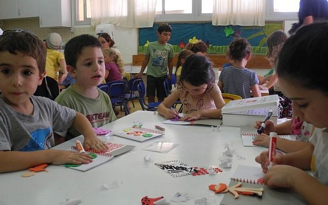Kids at Kibbutz Alumim decorate journals for their emergency art therapy kits on Wednesday.  (Melanie Lidman/Times of Israel)