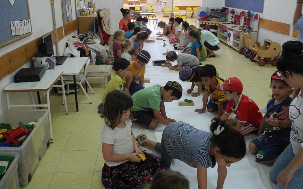 Children from Kibbutz Alumim in southern Israel make a mural of animals that make them feel strong, with Artists 4 Israel on Wednesday, August 13, 2014. (Melanie Lidman/Times of Israel)