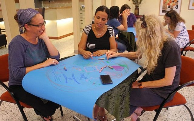 Parents from Kibbutz Alumim in southern Israel did their own art therapy with Artists 4 Israel, and then learned how to use the emergency art kits after sirens. (Melanie Lidman/Times of Israel)