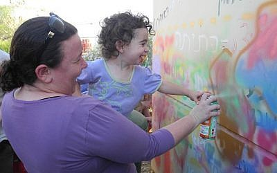 Kibbutz Alumim residents paint a bomb shelter with with members of the art advocacy group Artists 4 Israel on Wednesday. (Melanie Lidman/Times of Israel)