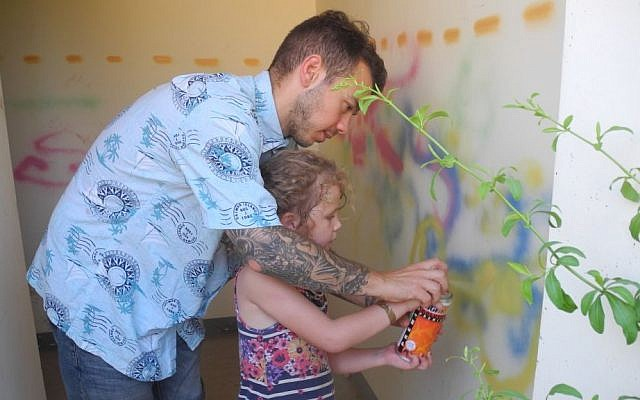 Artists 4 Israel director Craig Dershowitz paints the inside of a bomb shelter with a kid from Kibbutz Alumim on Wednesday.  (Melanie Lidman/Times of Israel)