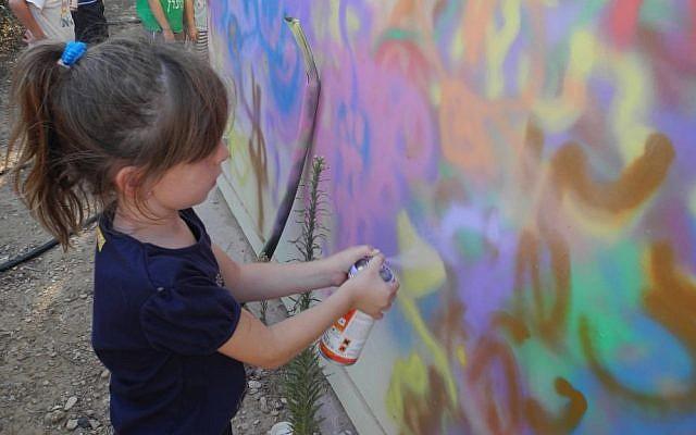 A girl at Kibbutz Alumim spray paints a bomb shelter with Artists 4 Israel.  (Melanie Lidman/Times of Israel)