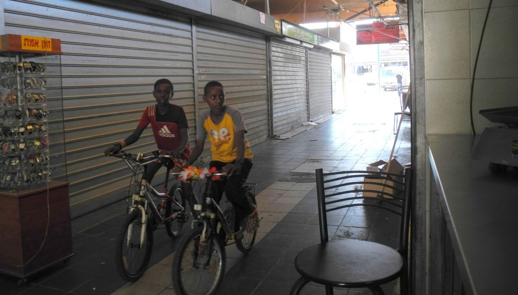 Children in Sderot ride their bikes through a mostly empty shuk on Wednesday afternoon. (photo credit: Melanie Lidman/Times of Israel)