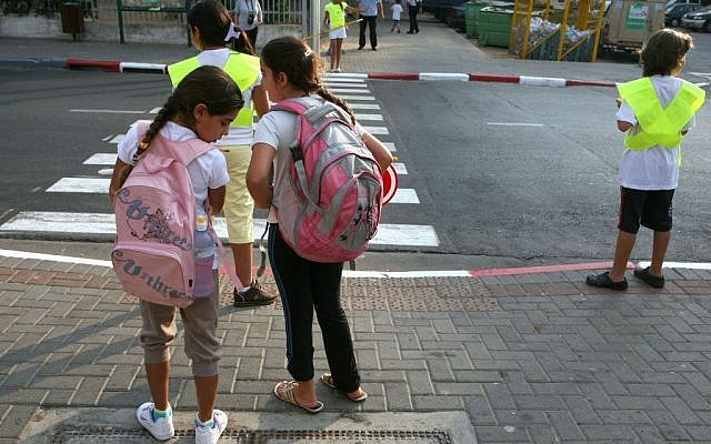 Illustrative: Schoolchildren waiting to cross a street. (Liron Almog/Flash90)