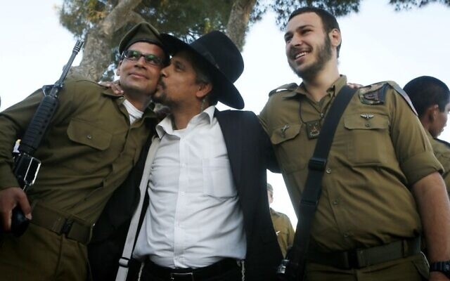 A religious Jewish soldier is embraced by an ultra-Orthodox Jewish family member after a swearing-in ceremony for the  IDF Nahal Haredi unit, at Ammunition Hill in Jerusalem, May 26, 2012 (Miriam Alster/Flash90)