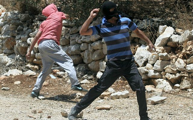 Illustrative photo of masked Palestinians throwing stones in the West Bank,  June 28, 2013. (Issam Rimawi/Flash90)