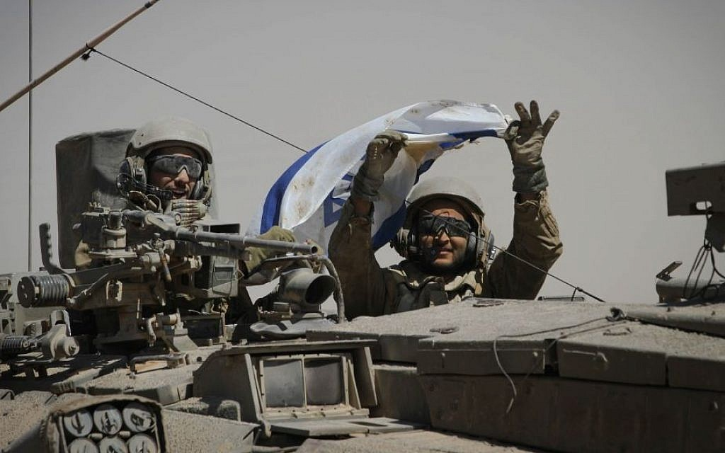 IDF soldiers hold up an Israeli flag as they ride in a tank along Israel's border with the Gaza Strip, Friday, August 1, 2014. (photo credit: Albert Sadikov/Flash90)