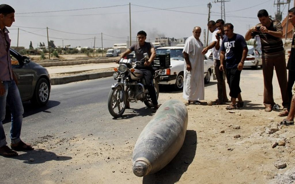 Palestinians look at an unexploded Israeli missile, which witnesses said was fired by an Israeli aircraft on a street in Deir El-Balah in the central Gaza Strip on August 01, 2014. (Photo credit: Mostafa Ashqar/Flash90)