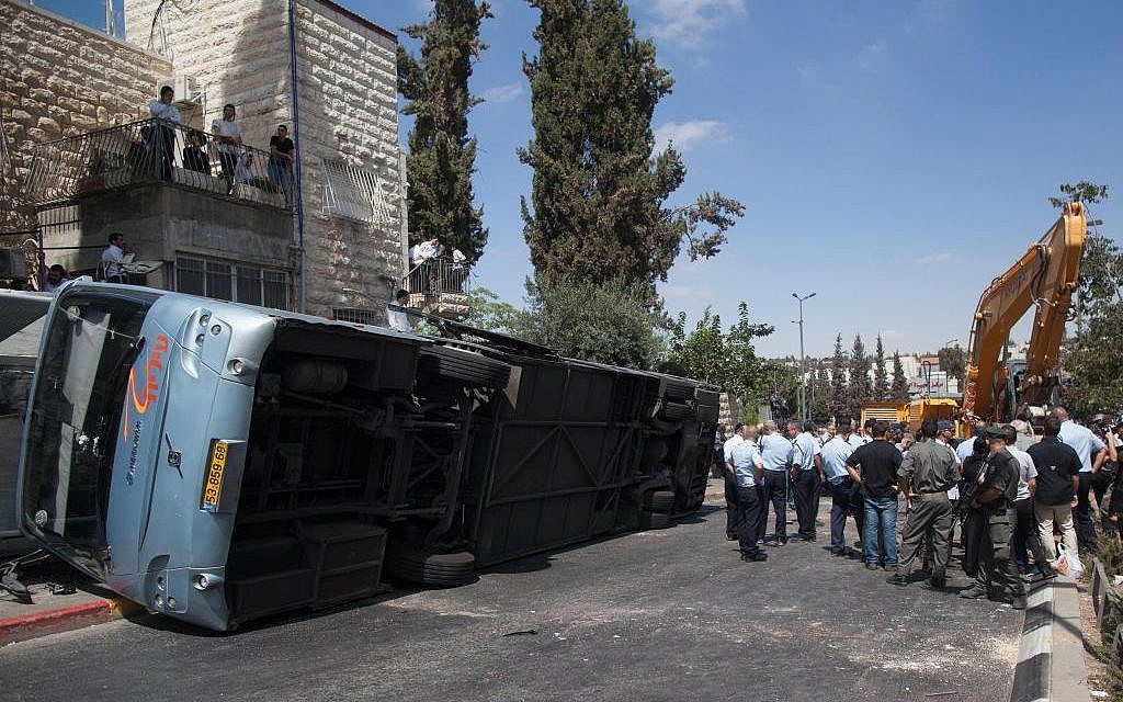 Security personnel at the scene where a tractor driver from the Arab neighborhood of Jabel Mukaber flipped over a bus on Shmuel HaNavi street in Jerusalem on Monday, August 4, 2014. (photo credit: Yonatan Sindel/Flash90)