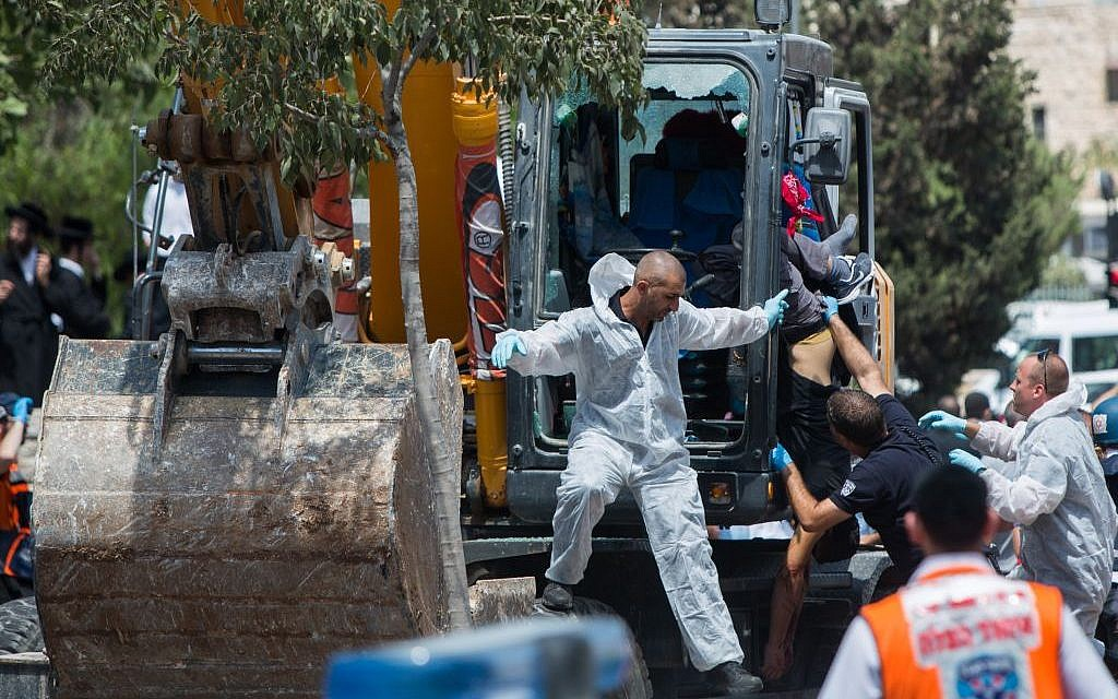 Security personnel extract the body of the Arab tractor driver shot dead by police after he drove into a pedestrian and flipped over a bus on Shmuel HaNavi street in Jerusalem on Monday, August 4, 2014.  (Photo credit: Yonatan Sindel/Flash90)