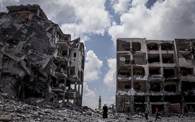 Palestinians walk in front of buildings destroyed by the Israeli military in the northern Gaza Strip town of Beit Lahiya, Monday, August 4, 2014. (Emad Nasser/Flash90)