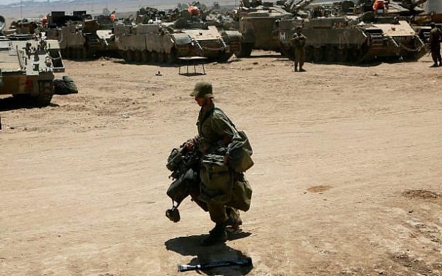 An IDF Israeli soldier carries army gear during a redeployment in southern Israel along the border with Gaza, August 06, 2014. (photo credit: Miriam Alster/Flash90)