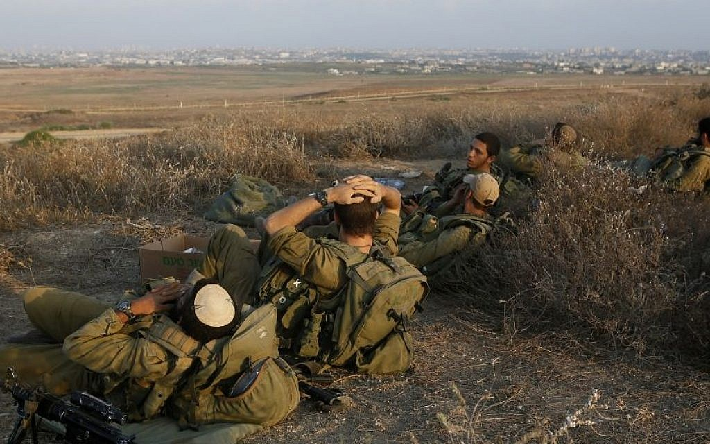 Israeli soldiers rest in southern Israel along the border with Gaza (background), August 06, 2014. (Photo credit: Miriam Alster/Flash90)