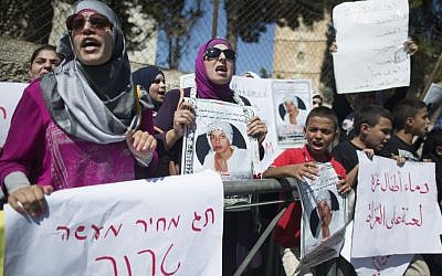 Arab protesters hold placards during a demonstration in support of the family of slain East Jerusalem teen Muhammed Abu Khdeir outside the Jerusalem District Court, Wednesday, August 6, 2014. (photo credit: Yonatan Sindel/Flash90)