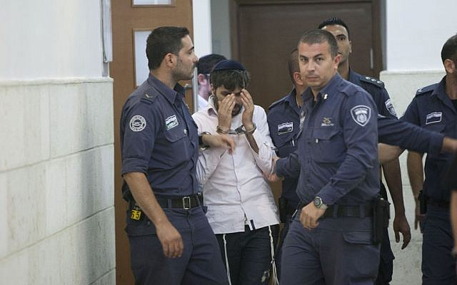 Police escort Yosef Haim Ben-David, one of the Jewish suspects of the murder of Muhammad Abu Khdeir, in the Disctrict Court in Jerusalem, Wednesday, August 6, 2014 (photo credit: Yonatan Sindel/Flash90)