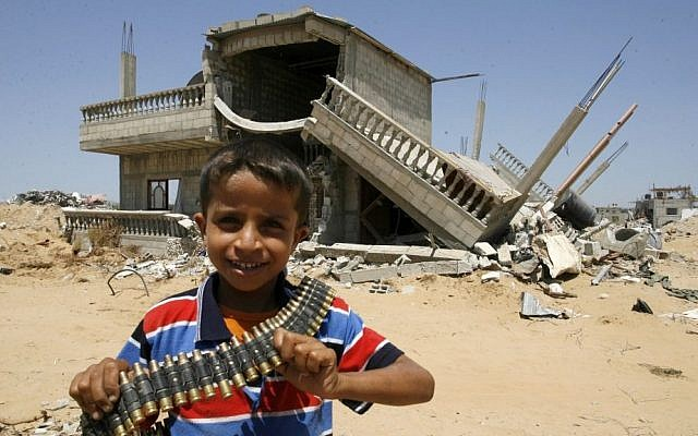 A Palestinian boy holds an Israeli bullet belt close to the border between Israel and the Gaza Strip, east of the southern Gaza Strip town of Khan Yunis on August 7, 2014. (photo credit: Abed Rahim Khatib/Flash90)
