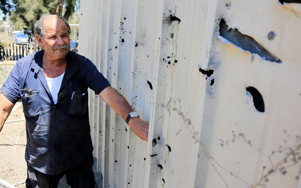 A man inspects the damage caused by a rocket that exploded near Israel's border with the Gaza Strip on Friday, August 8, 2014. (photo credit: Edi Israel/Flash90)