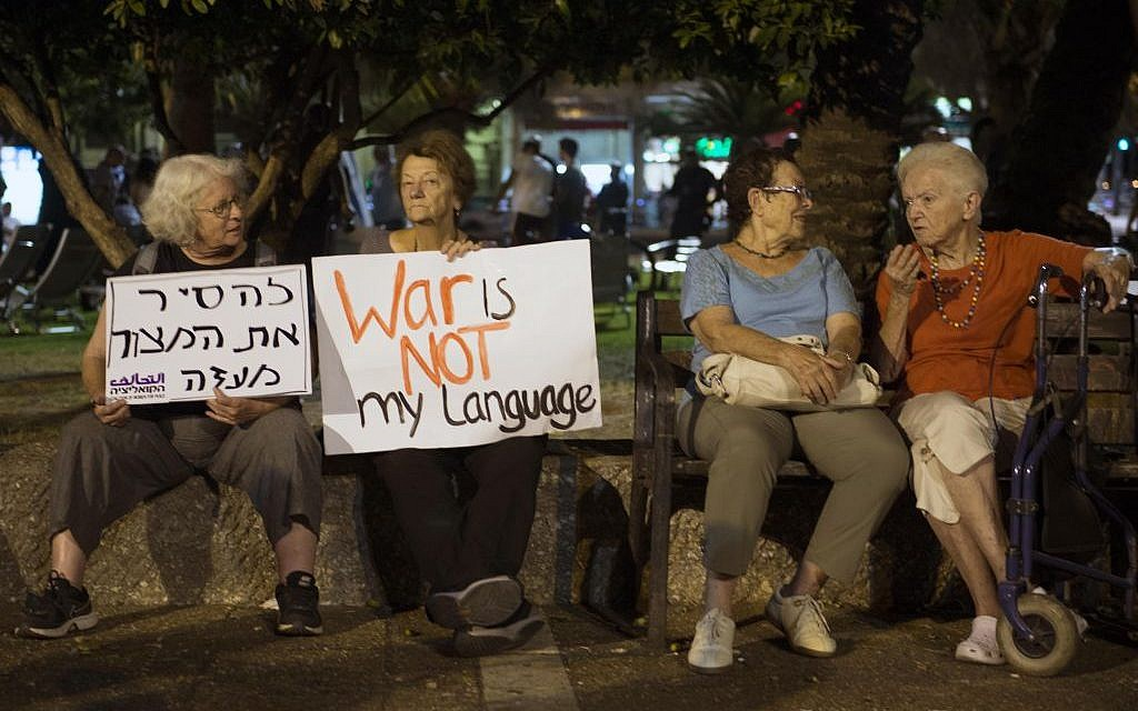 Israeli left wing activists hold placards during a demonstration against Israel's offensive in the Gaza Strip, in Tel Aviv, Israel, Saturday, August 9, 2014. (Photo credit: Danielle Shitrit/Flash90)