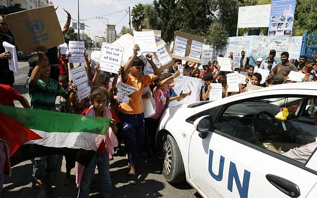 Palestinian children hold posters outside an UNRWA school in Gaza during a protest on August 11, 2014. (Abed Rahim Khatib/Flash90)