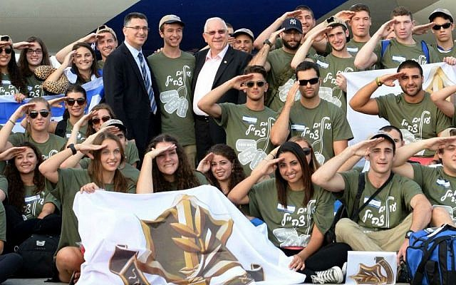 Israeli president Reuven Rivlin (C) and Minister of Interior Affairs Gideon Saar (center left) welcome new immigrants from USA and Canada as they arrive in a special 'Soldier Aliyah Flight 2014' on behalf of the Jewish Agency and the Nefesh B'Nefesh organization, at Ben-Gurion Airport, August 12, 2014. (Israeli Defense Force).  (Mark Neyman/GPO/ FLASH90)