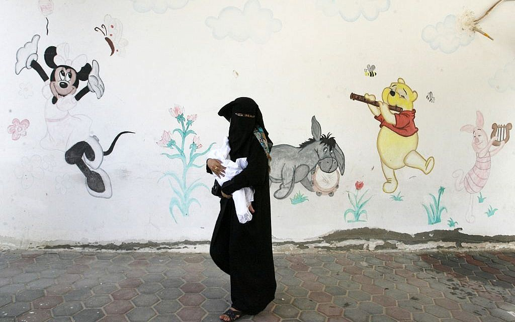 A Palestinian woman holds her baby, who war born in a shelter during the Israeli offensive, during a ceremony to honor the mothers in an UNRWA center in Rafah refugee camp, in the southern Gaza Strip on Wednesday, August 13, 2014 (photo credit: Abed Rahim Khatib/Flash90)