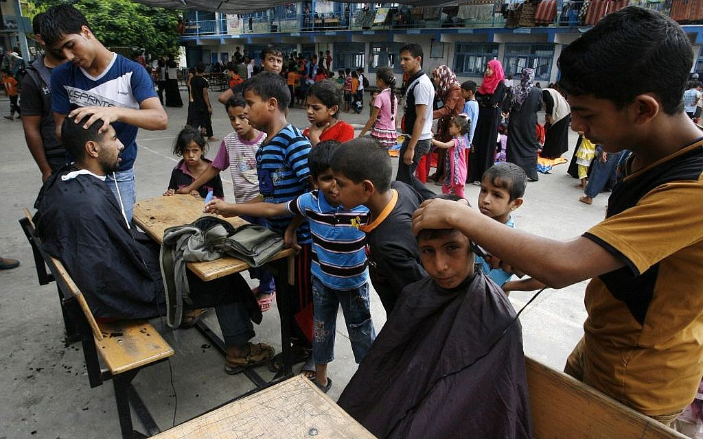 Palestinians get hair cuts at an UNRWA school in Rafah where they have taken shelter, August 17, 2014 (Abed Rahim Khatib/Flash90)