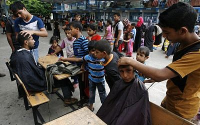 Palestinians get hair cuts at an UNRWA school in Rafah where they took shelter during the Gaza war, on August 17, 2014 (Abed Rahim Khatib/Flash90)