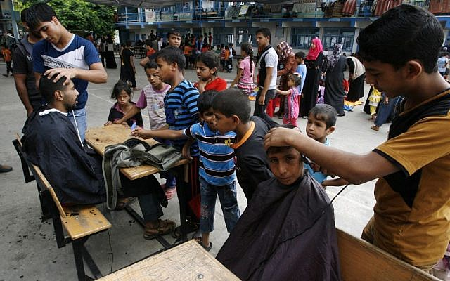 Palestinians get hair cuts at an UNRWA school in Rafah where they have taken shelter, August 17, 2014 (photo credit: Abed Rahim Khatib/Flash90)