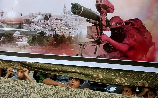 Palestinian children look on from behind a banner at a pro-Hamas rally in Rafah, southern Gaza Strip, August 17, 2014 (photo credit: Abed Rahim Khatib/Flash90)