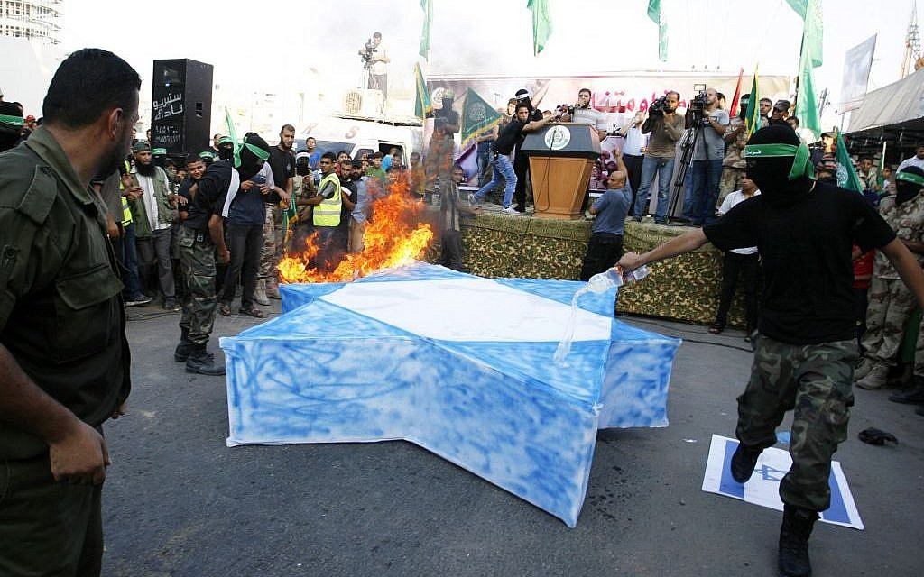 Masked Hamas members burn a cut-out of a Star of David during a Hamas demonstration August 17, 2014 in Rafah, Gaza Strip. (Photo credit: Abed Rahim Khatib/Flash90)