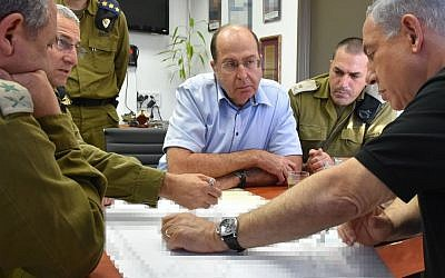 Prime Minister Benjamin Netanyahu, right, and Defense Minister Moshe Ya'alon, opposite, seen during a visit at Ashdod Port on August 18, 2014. (Photo credit: Ariel Hermoni/Ministry of Defense/Flash90)