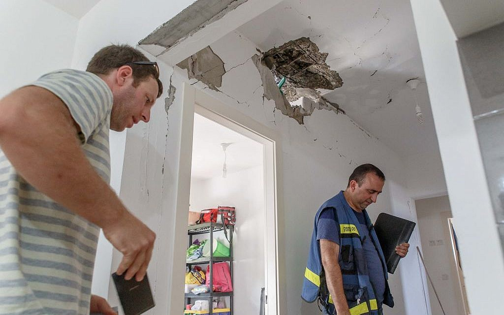 Tax authority workers survey the damage caused to a house after it was hit by a rocket in the Hof Ashkelon Regional Council on August 20, 2014. (Photo credit: Flash90)