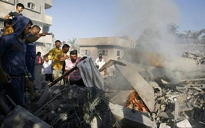 Palestinians gather around the rubble of a house, which witnesses said was destroyed in an Israeli air strike, in Rafah in the southern Gaza Strip on August 20, 2014. (photo credit: Abed Rahim Khatib/Flash90)