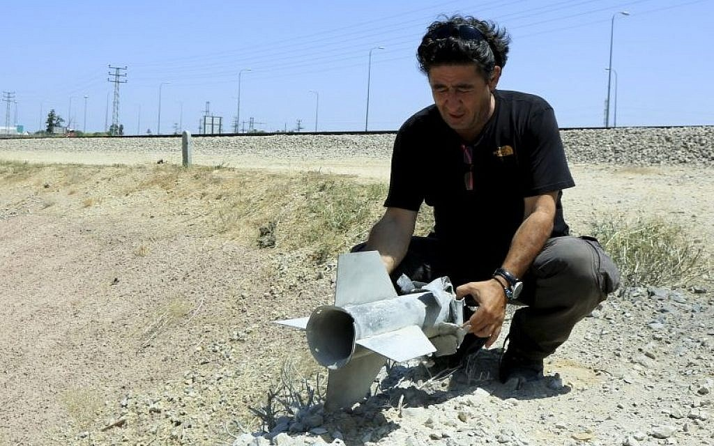 Illustrative. A man holds part of a rocket that exploded and fell inside the Israeli border with the Gaza Strip on August 20, 2014. (photo credit: Edi Israel/Flash90)