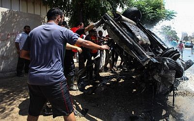 Palestinians around a destroyed vehicle after an Israeli airstrike in Gaza City on August 24, 2014. (photo credit: Emad Nassar/Flash90)