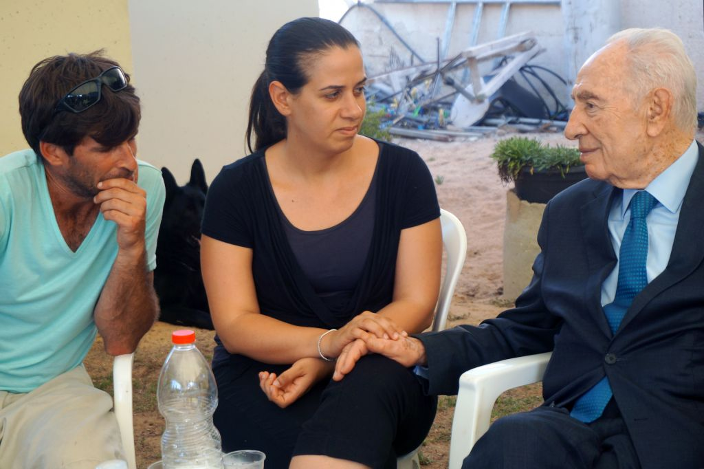 Former president Shimon Peres with Doron and Gila Tragerman, the parents of 4-year-old Daniel, at Kibbutz Nahal Oz on August 24, 2014. Daniel was killed by a mortar shell fired from Gaza on August 22. (Photo credit: Flash90)