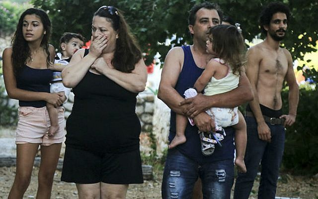 Residents look on in shock after a rocket fired from the Gaza Strip hit a house in Ashkelon, southern Israel, early morning on August 26, 2014. (photo credit: Edi Israel/Flash90)