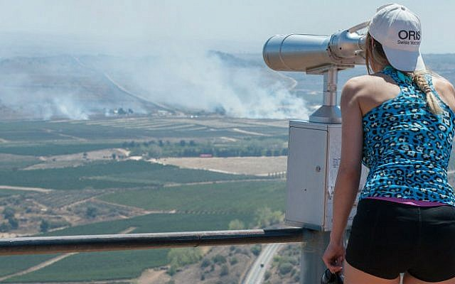 An Israeli woman looks on as smoke rises near the Quneitra Crossing as seen from the Israeli Golan Heights August 27, 2014. (photo credit: Flash90)