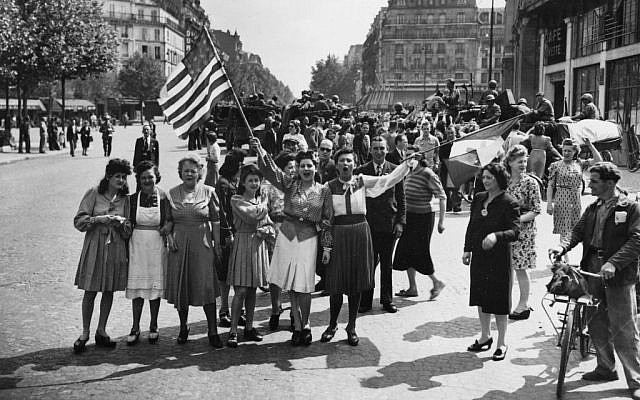 "This Aug. 25, 1944 file photo shows French civilians with their hastily made American and French flags singing the ""Star Spangled Banner"" as they greet U.S. and Free French troops entering Paris, France, after Allied liberation of the French capital from Nazi occupation in World War II. (photo credit: AP Photo/Harry Harris, file)"