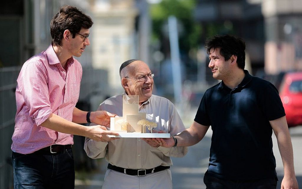 In this Friday, July 4, 2014 photo, Protestant priest Gregor Hohberg, Rabbi Tovia Ben-Chorin and Imam Kadir Sanci, from left, show a model of the planned prayer and education building House of One prior to an interview with The Associated Press in Berlin. House of One will house a synagogue, a Christian church and a mosque. (AP Photo/Markus Schreiber)