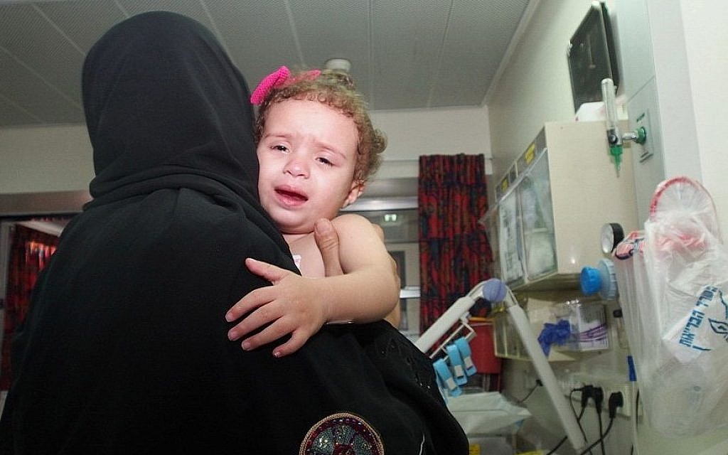 Two-year-old Hala Arada with her grandmother Haniyah Shaer at Wolfson Hospital in Holon, August 12, 2014. Hala has congenital heart disease and is being treated in Israel. Two members of her family were recently killed in an Israeli air strike in Gaza.  (photo credit: Sheila Shalhevet/Save a Childs Heart)